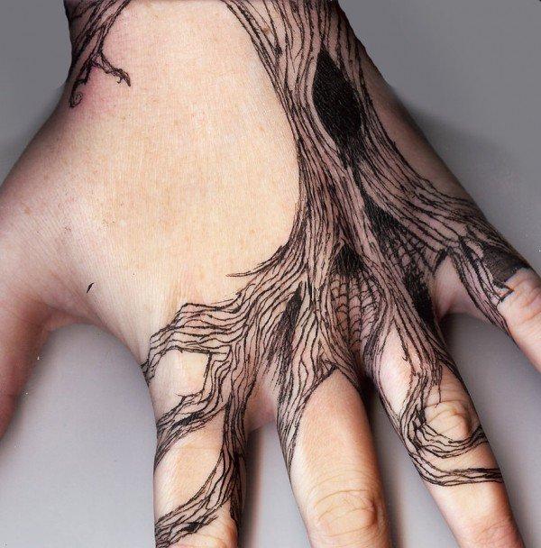 vemos una mano de mujer con un tatuaje de arbol seco