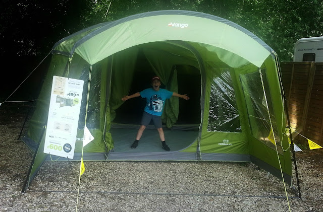 Boy standing inside brand new tent.