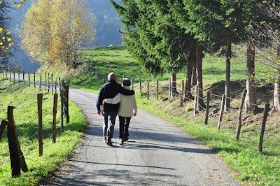 Ein älteres Ehepaar, das Arm in Arm über eine Straße geht. Rechts und links der Straße sind grüne Wiesen und ein paar Bäume