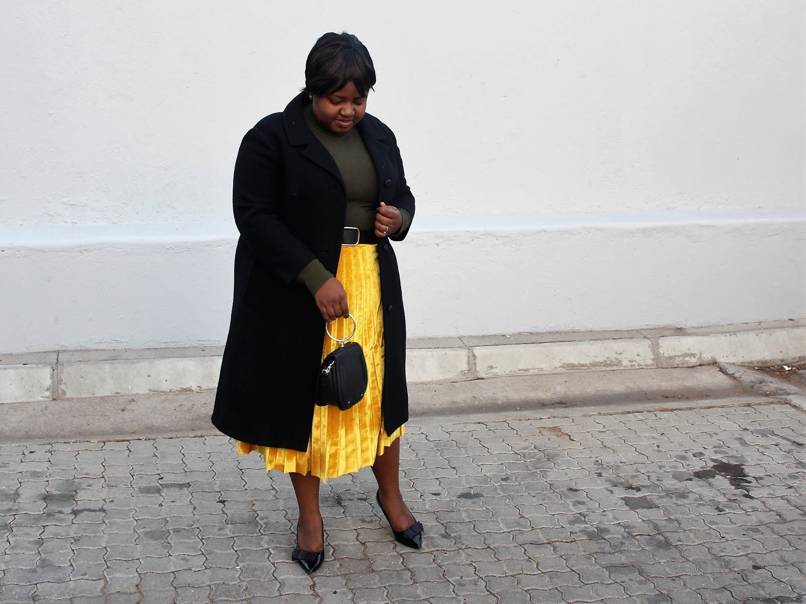 Black coat and mustard yellow skirt
