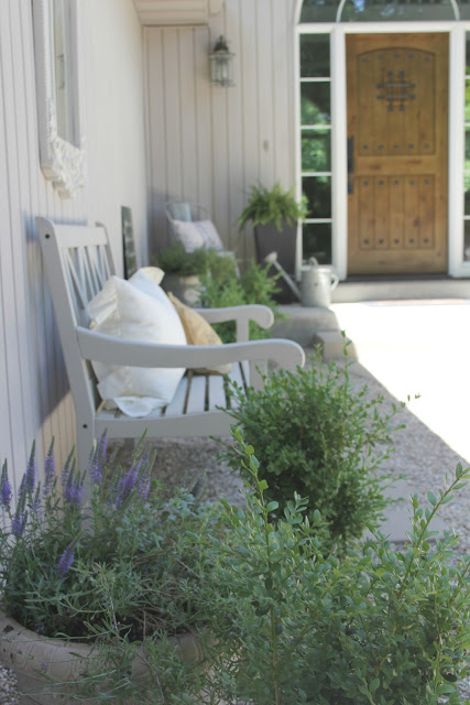 French country Provence inspired pea gravel courtyard with boxwood, bench, and vintage decor by Hello Lovely Studio