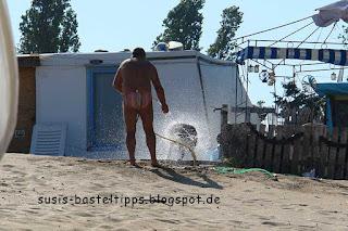 ein Hund wird am Strand mit Schlauch abgespritzt