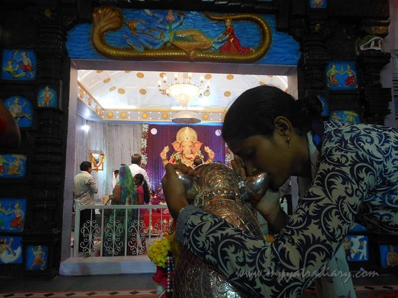 A girl whispers in mouse ears at Andhericha Raja life size Ganesha pandal, Mumbai