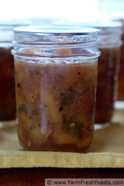 a side view of a jar of peach salsa with roasted Hatch chiles and golden plums