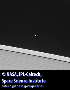 Saturn's Atlas moon in the distance and Saturnian rings in the foreground