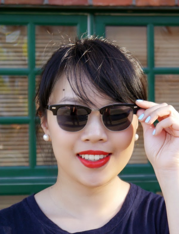 Pearl earrings, orange-red lipstick, powder blue nails, classic sunglasses