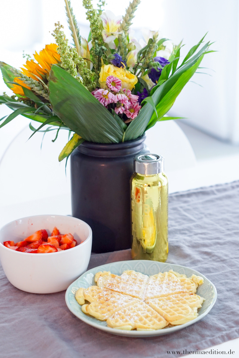 Waffeln mit Erdbeeren im Hintergrund schwarze Vase von Sostrene Grene mit buntem Blumenstrauß