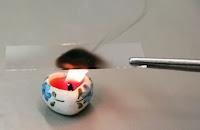 Cımbızla tutulan bir lam camına altında yanan bir mumun isinin çıkması