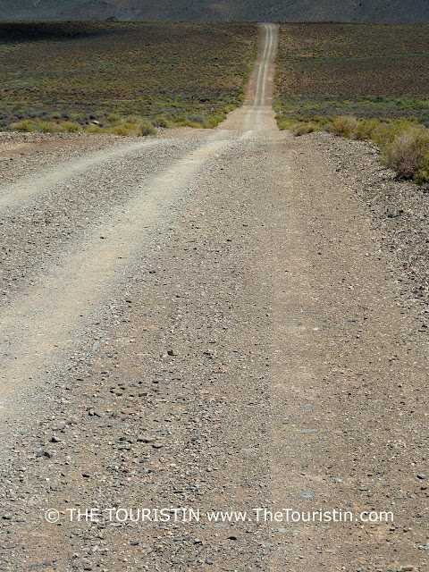 Gravel Road through a flat landscape towards green hills.