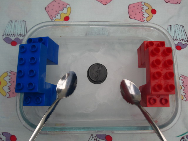 Lego on the bowl of ice set up like an ice hockey game with spoons for sticks and the bottle top for a puck