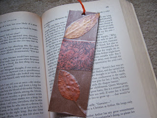 An open book with a bookmark with autumn leaves on it.