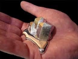 Metal galio fundiendo por el calor de la mano, hay un bloque de metal en la palma de una mano, parte del metal está sólido y la otra parte está líquida, es muy parecido al mercurio.