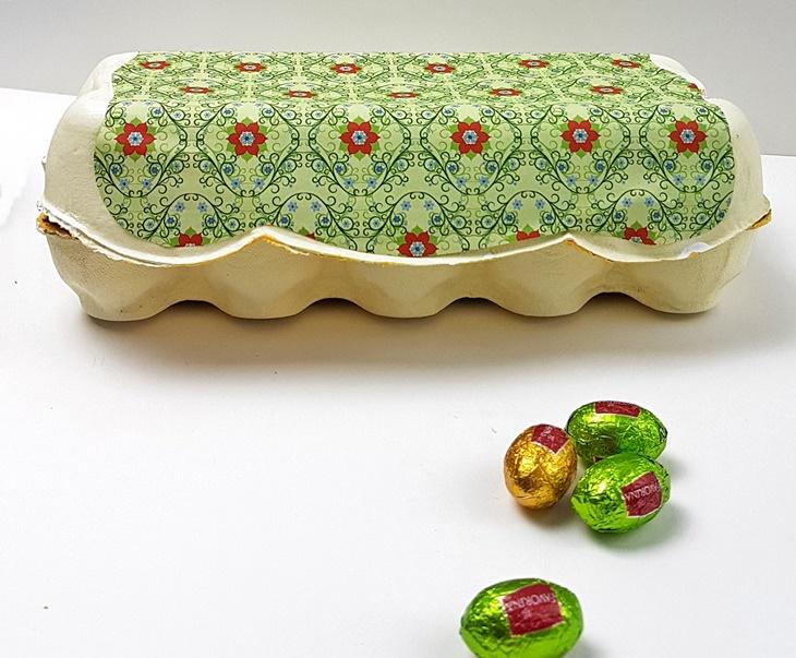 bemalter und beklebter Eierkarton und Schokoladeneier