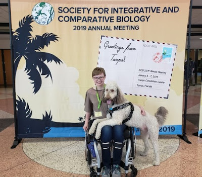 "Amy-Charlotte Devitz and service dog Fisher in front of a ""Society for Integrative and Comparative Biology"" sign."