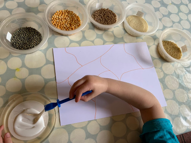 Set up showing bowls of grains and pulses, glue and card with a toddler ready to go