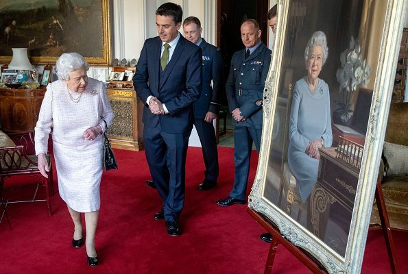 The Queen is wearing a brooch presented to her by the RAF Regiment. Queen Elizabeth II viewed a new portrait at Windsor Castle