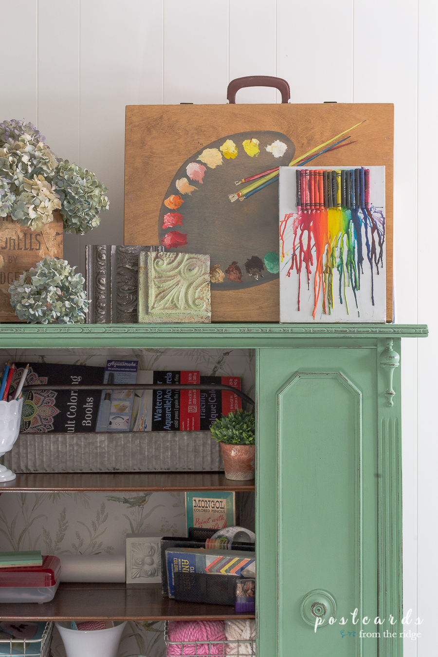 artist supplies and vintage accents in a green painted vintage China cabinet