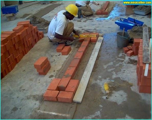 pedreiro assentando tijolos