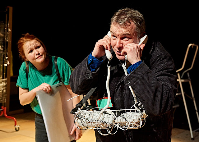 A man with a basket of phones, plus one held to each ear and a girl in green looking at him.