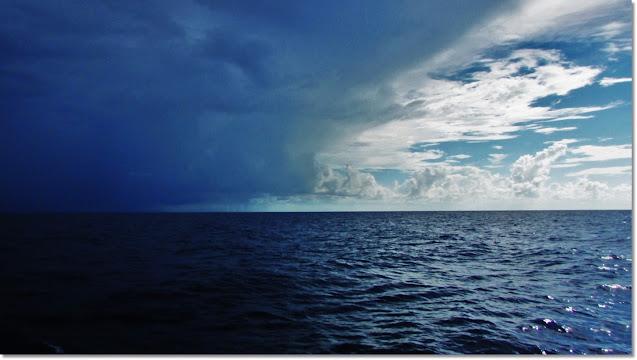 An ocean horizon is split between bright blue skies and encroaching dark storm clouds casting a shadow across the water.