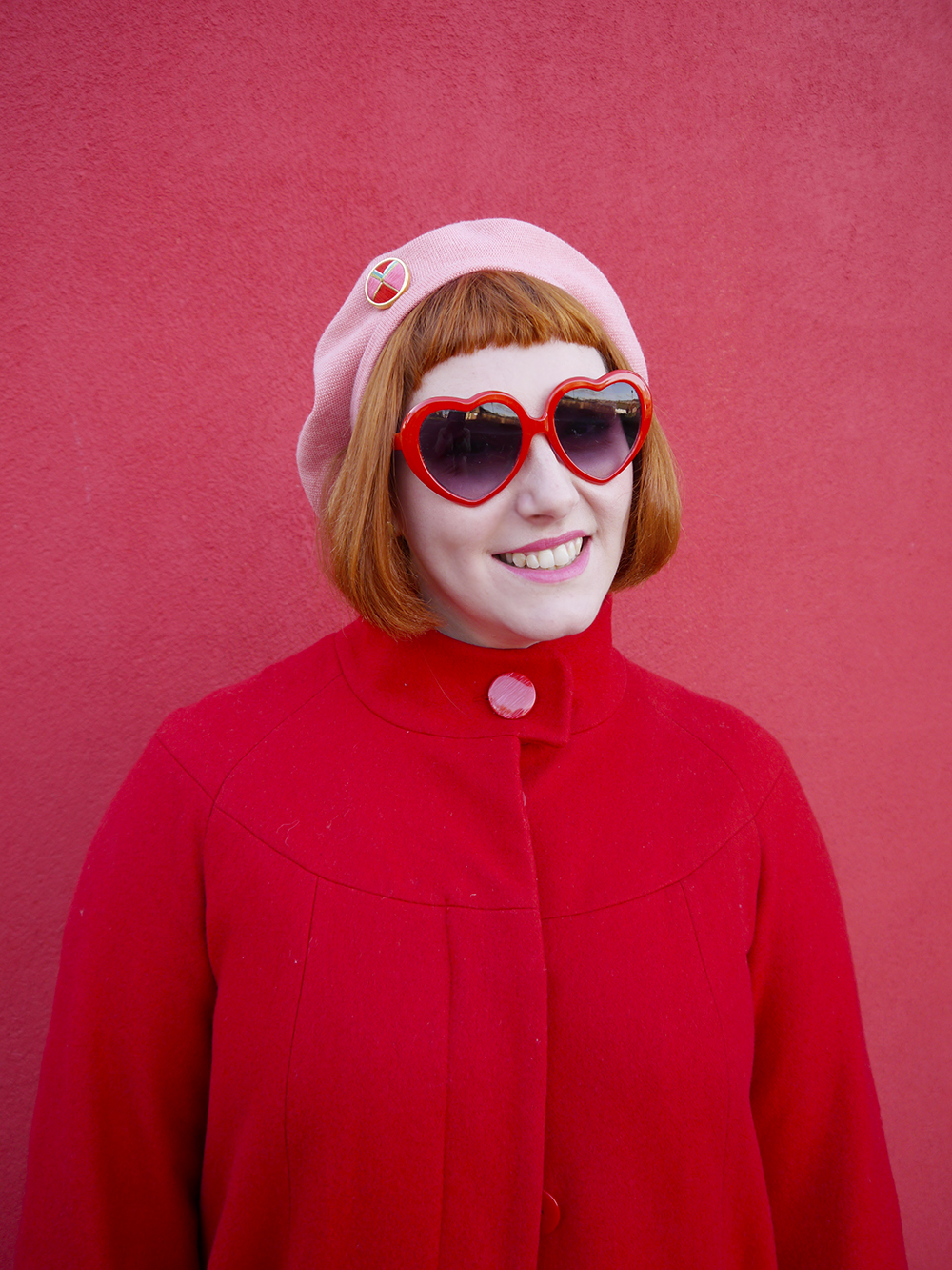 Scottish bloger, Helen from Wardrobe Conversations wears a red coat, red heart sunglasses and a pink beret