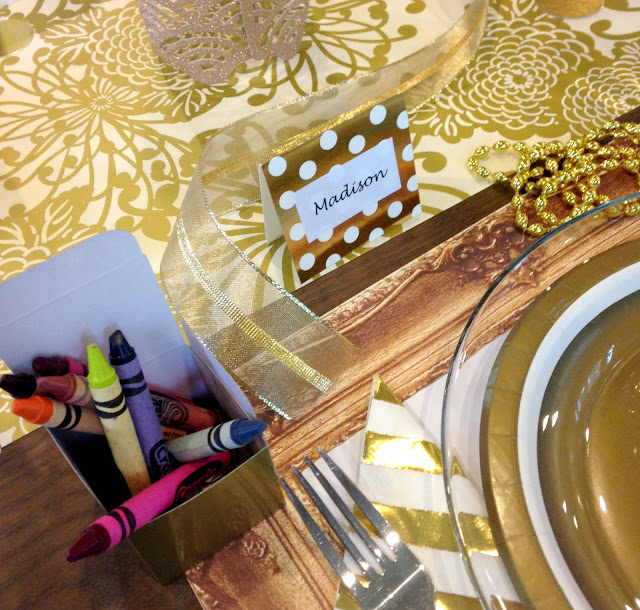 Gold themed party set for a kid.  Crayons and coloring placemat.