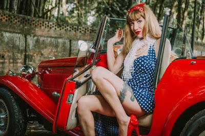 As linhas e a cor vermelha do carro combinam perfeitamente com a sensualidade da pinup.