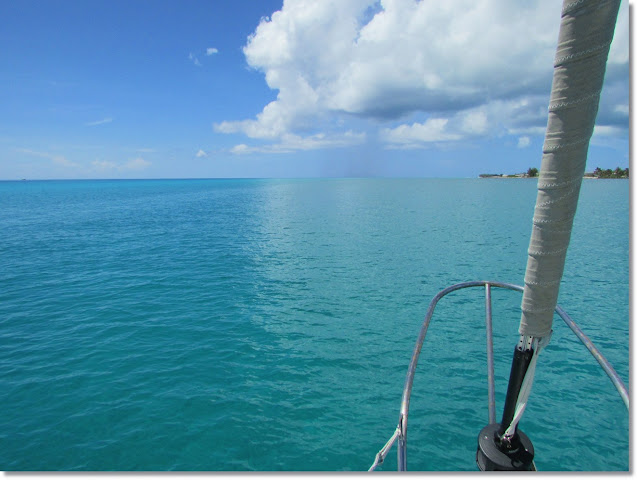 Flat turquoise ocean horizon meets shore of Bimini. The sky on the left is clear blue. On the right, rainclouds encroach.