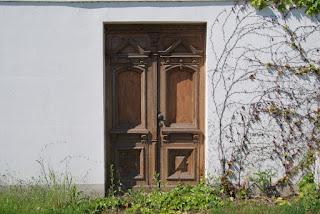 Eine hölzerne und verzierte Tür, die in eine weiße Wand eingelassen ist. Die Tür endet einfach vor einer Wiese
