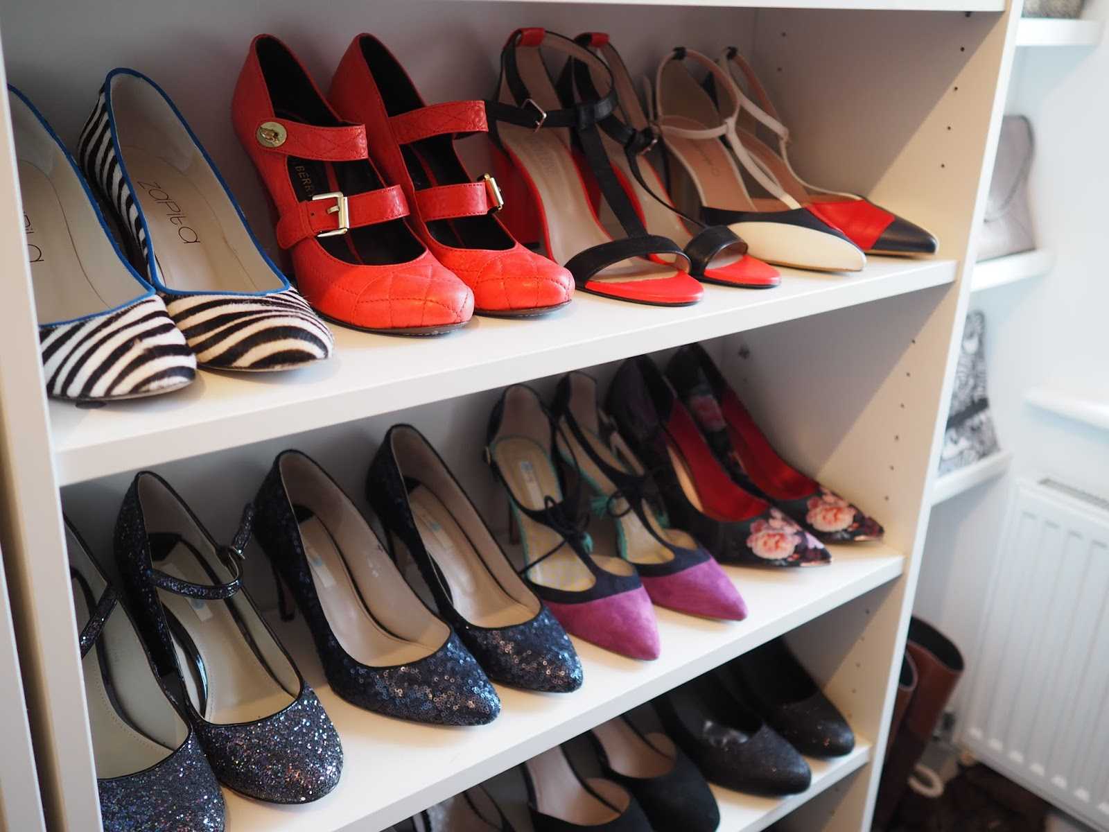 Walk in closet with white Ikea Billy bookcase to store coloured shoes