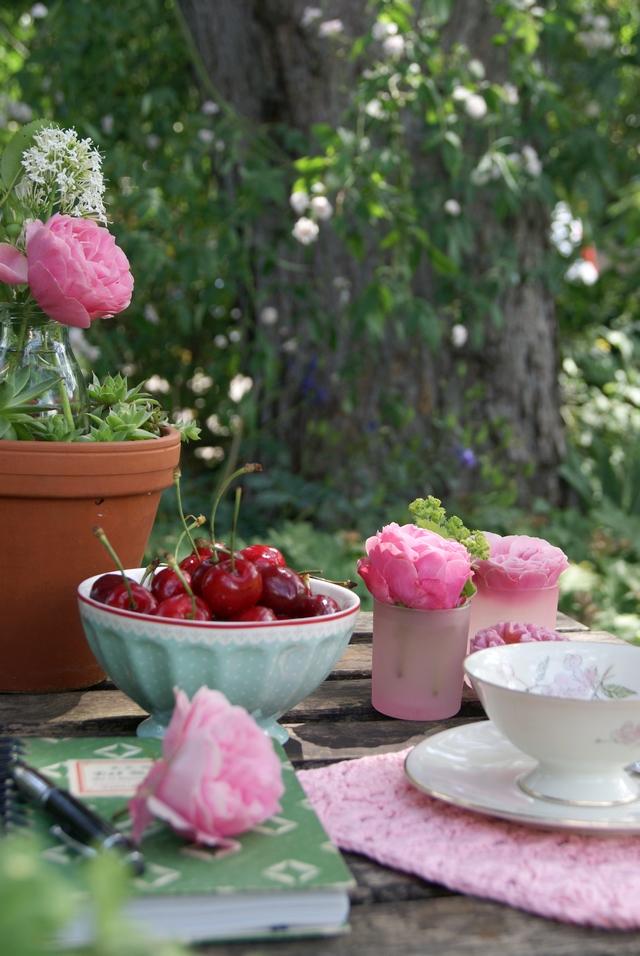 Gartentisch mit Gedeck und Rosendekoration