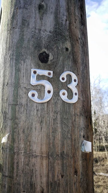 Tin numbers attached to a wooden power pole from www.ruralmag.com