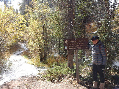 A lady hiking on a fall day in a winter coat, gloves, hat, and boots.