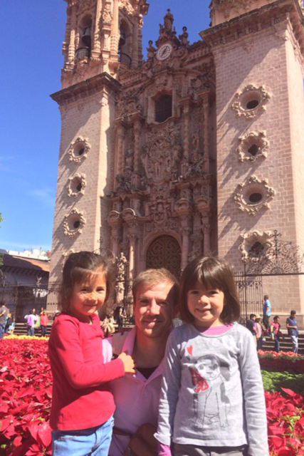 Expat, Nomad, Immigrant: Stories From Life Abroad A Guest Post Series Featuring Lu En Aparté - Image Shows A Man With His Two Daughters In Front Of A Colonial Mexican Church