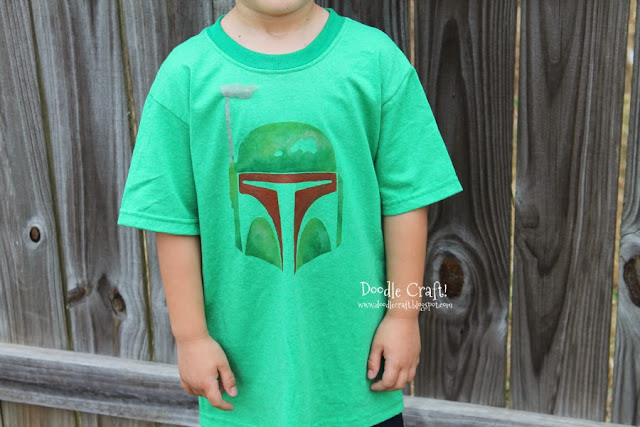 """Boba Fett Stenciled Shirt  I love using my Cricut for custom shirts, but you can do it without a fancy machine too! You will need freezer paper, it's about $6 at Walmart and will last you forever. Just use a hobby knife to cut out your desired design. Then iron the shiny side onto the shirt...and this shirt we found """"slightly irregular"""" at the dollar store. Then use the freezer paper as a stencil and add paint!  Great for tote bags, pillowcases, cosmetic bags, shirts and more!"""