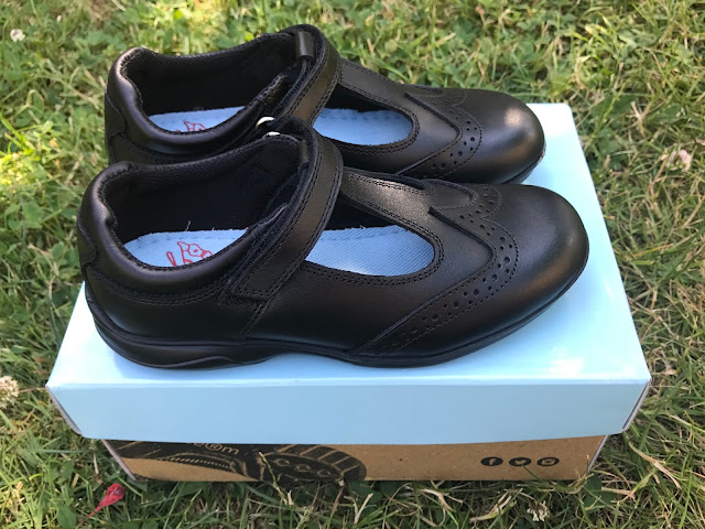 A pair of black t-bar school shoes on a shoe box