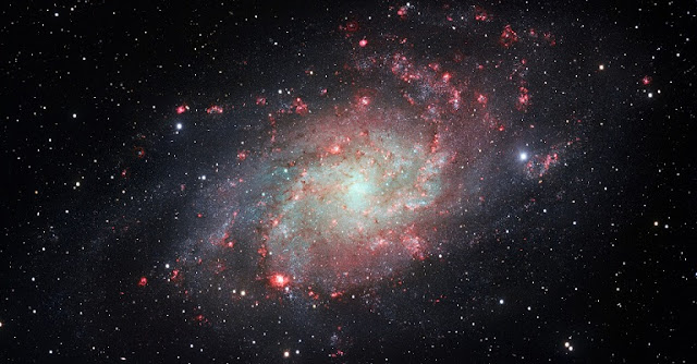 Image of the Triangulum Galaxy (M33) taken by the VLT Survey Telescope (VST), at ESO's Paranal Observatory. Even in this normal spiral galaxy, nebular emission (shown in red) provides locally an important fraction of the optical luminosity, especially in HII regions and spiral arms. (Credit: ESO)