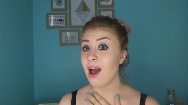 a girl with blonde hair, blue eyeshadow and cat eyeliner looking at the camera, shocked, with a selection of feature frames behind her, on a turquoise wall behind the girl. The girl is francesca sophia