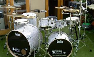 """Sejarah Alat Musik Drum  Sejarah alat musik drum berlanjut perkembangan alat musik drum. Seperti Gembrengan dan Tom tom yang berasal dari Cina mulai ditambahkan ke drum kit atau drum set. Dari situ kemudian ditambahkan lagi alat-alat musik lainnya. Di athun 1930-an, drum kit telah dibuat dalam berbagai bentuk. Kemudian dalam sejarah alat musik drum, di tahun 1960-an, perkembangan drum kit mulai melesat, dan ini berawal dari munculnya para pemain drum beraliran musik rock. Drum kit kembali ditambahkan, seperti tambahan tom-tom dan juga bass drum lainnya, atau double bass drum. Dan perkembangan sejarah alat musik drum di era modern juga melahirkan drum elektonik yang dapat menghasilkan berbagai jenis suara. Dengan semakin berkembang nya teknologi internet, situs suog.co berusaha untuk memberikan informasi yang berkaitan dengan sejarah di dunia, khususnya kesenian. Situs suog.co memiliki ratusan artikel kesenian tari dan alat musik tradisional misal """" Sejarah asal usul dan perkembangan alat musik drum """" yang di anda jadikan masukan atau bahan referensi ilmu pengetahuan anda.                                            Pencipta alat musik drum – Alat musik drum dimulai dengan munculnya peradaban manusia. pukulan drum telah dikaitkan dengan kelahiran manusia. drum adalah salah satu jenis alat musik yang dulu di"""