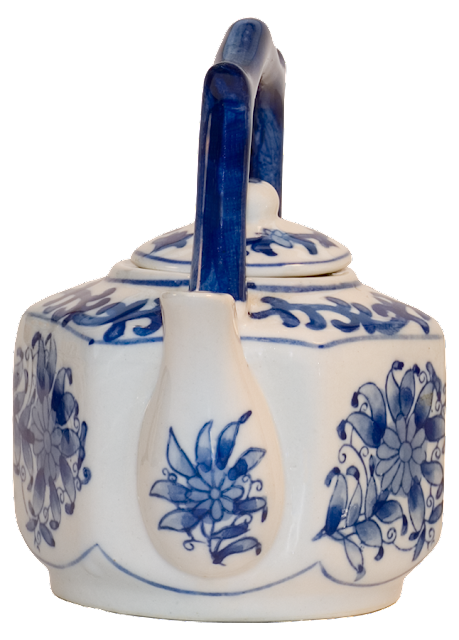 Small teapot viewed from the front showing a blue flower on the spout.