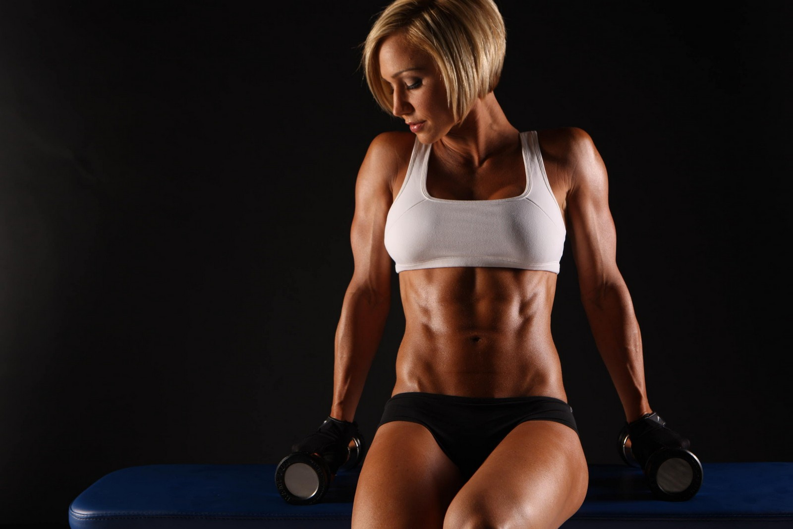 A fit girl seating on table