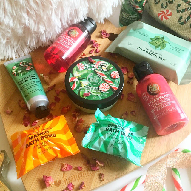 Body shop flatlay, peppermint scrub and hand cream, exfoliating soap, strawberry shampoo and conditioner