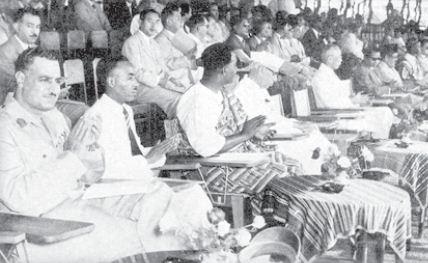 Para anggota delegasi dari berbagai negara Asia dan Afrika sedang menyaksikan atraksi kesenian di Bandung. Tampak Gamal Abdul Nazer (Presiden Mesir) di sebelah kiri.