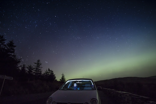 Woman sitting in a car at night and the Aurora Borealis in the night sky behind