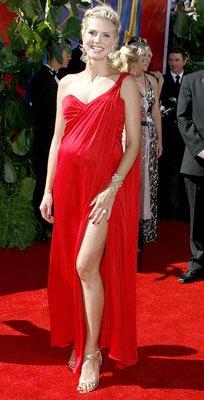 Foto de mujer luciendo vestido de maternidad color rojo con escote y abertura en la pierna