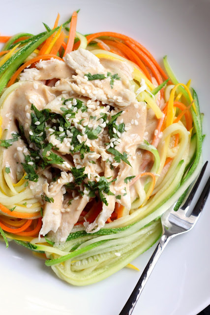 Close up of Zucchini Noodles with Chicken and Tangy Peanut Sauce in a white bowl