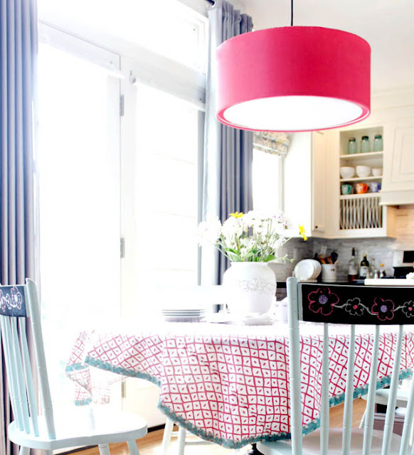 kitchen table with tablecloth, pink drum light, blue chairs