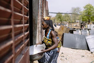 Carrying shea to the cooking area in Burkina Faso.