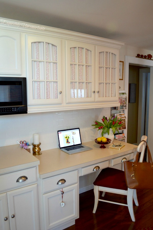 Charming kitchen desk area with fabric covered cabinets