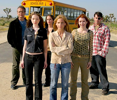 Group shot of actors portraying Buffy, Dawn, Xander, Willow, Faith, and Giles from the series finale, in desert with school bus